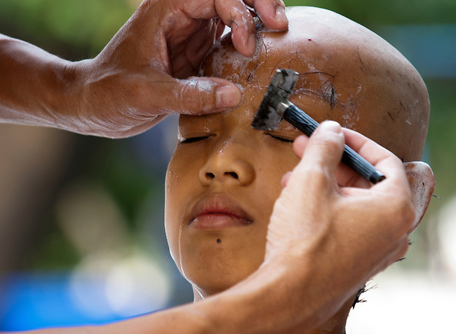 April 1, 2012, Saraburi, Thailand. Pre-teen boys get their heads shaved as they go through the process of becoming a Novice.