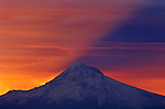 Mount Hood 3426m (11,239ft) casts its own shadow at sunrise, viewed from Mount Tabor Park in Portland.  The left skyline is Cathedral Ridge, and the right skyline is the Southeast Ridge.  The bulge in the Southeast Ridge is called the Steel Cliff.  Mount Hood is a stratovolcano in the Cascade Volcanic Arc of Northern Oregon.  The mountain's twelve glaciers are thinning as a result of glacial retreat attributed to Global Warming associated with World Climate Change.  Nikon F4, AF300/4. Kodak E100VS