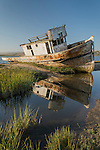 Inverness Park, Point Reyes National Seashore, California; a wooden fishing boat is beached on a sandbar at the edge of Tomales Bay in late afternoon sunlight