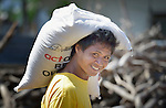 A young man carries a bag of food and other relief supplies home following a distribution of the material to survivors in Estancia, a village in the Philippines that was hit hard by Typhoon Haiyan in November 2013. The storm was known locally as Yolanda. The food items were provided by the National Council of Churches of the Philippines, a member of the ACT Alliance.