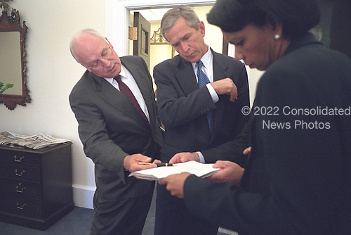 United States President George W. Bush looks over a brief with U.S. Vice President Dick Cheney and National Security Advisor Dr. Condoleezza Rice outside the Oval Office at the White House in Washington, D.C. on Wednesday, September 12, 2001..Mandatory Credit: Eric Draper - White House via CNP.