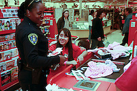 Detective Brenda Richmond of San Diego Police Department's Central Division with two of the three hundred disadvantaged children who took part in the annual Shop-With-a-Cop event at the Sports Arena Target store in San Diego on December 1, 2007.  Many of the children rose well before dawn in order to be ready for the fleet of buses that collected them from every corner of the county.  The buses took them to SeaWorld where they were paired up with an officer for the event.  After breakfast they made their way to the Target store in a huge, convoy of more than three hundred police vehicles with sirens blaring, lights flashing and Santa waving from a police helicopter hovering above them.  Each child had a $100 gift card to spend and many of them resisted the temptation to buy toys and choose instead to get clothes for themselves, their siblings or parents.