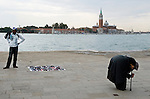 Venice Italy 2009. North African man selling fake sunglasses. Rumanian gypsy woman disguisers herself and begs money from passing tourists, many of whom as they are only in Venice for the day believe that she is a poverty stricken old aged Italian.  San Giorgio Maggiore in background. Canal di San Marco.<br /> <br /> Venice is sinking under the weight of 20 million visitors a year. Only 30% of Venice's visitors stay overnight the rest stay out of town or on their cruise ships. There is a plan is to limit visitors to the city who have pre-booked hotel accommodation.