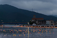 Lanterns float down the river to the sea. Each represents a human soul. Ishinomaki Kawabiraki Festival, Ishinomaki, Miyagi Prefecture, Japan, July 31, 2013. The Ishinomaki Kawabiraki Festival has been held annually since 1916 to honour Magobe Kawara an engineer who was instrumental in building the city's port and sea defences, as well as mourn those lost at sea. In recent years, the festival has commemorated the victims of the March 2011 earthquake and tsunami.