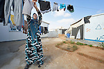 A woman hangs laundry outside her home in the Zaatari refugee camp near Mafraq, Jordan. Established in 2012 as Syrian refugees poured across the border, the camp held more than 80,000 refugees by 2015, and was rapidly evolving into a permanent settlement, with many refugees moving out of tents and into modular houses. The ACT Alliance provides a variety of services to refugees living in the camp.