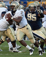 Navy quarterback Ricky Dobbs (4) is pursued by Pitt lineman Mick Williams (95). The Pittsburgh Panthers defeated the Navy Midshipmen 27-14 at Heinz Field, Pittsburgh, PA.