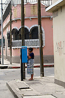 Maya woman using a pay telephone in downtown, Guatemala City, Guatemala.
