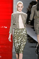 Hannare walks runway in a rustic northwood short cropped jacket with gold embroidered pocket detail over ivory sleeveless Chantilly lace mock turtleneck and gold three-dimensional pinwheel embroidered skirt, from the Reem Acra Fall 2012 Feminine Power collection fashion show, during Mercedes-Benz Fashion Week New York Fall 2012 at Lincoln Center.