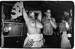 "June 15, 1988:  A topless woman holding a sign which says ""sex"" having fun at the Celebrity Club at Tunnel nightclub in New York City, New York."