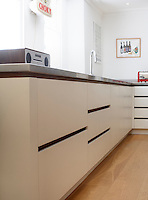 The simple contemporary kitchen units are topped with a practical stainless-steel work surface