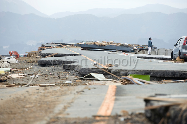 A man looks out over the battered landscape from Route 45 that once passed through Rikuzen-Takata City, Iwate Prefecture on  21 March 20011.  .Photographer: Robert Gilhooly