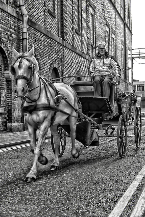 A black and white view of a horse and carriage going by the Guinness Brewery in Dublin Ireland.