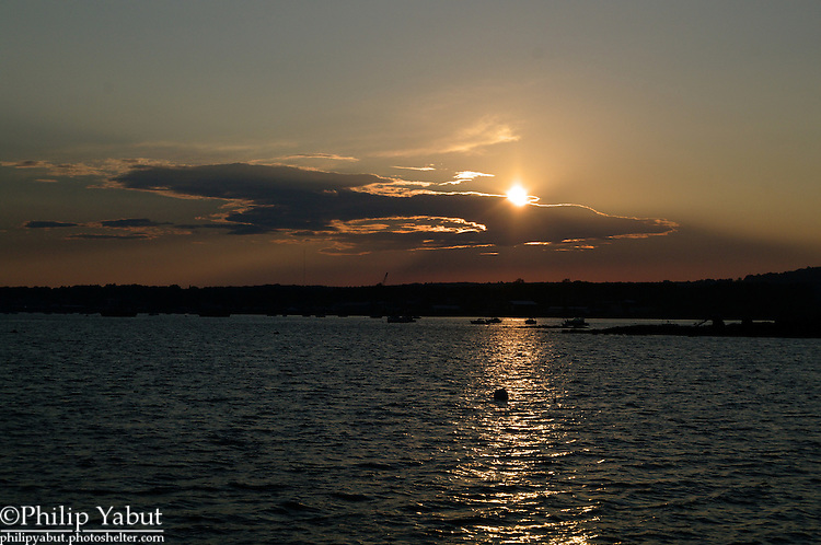 The sun begins to set over Rockland Harbor, Maine.