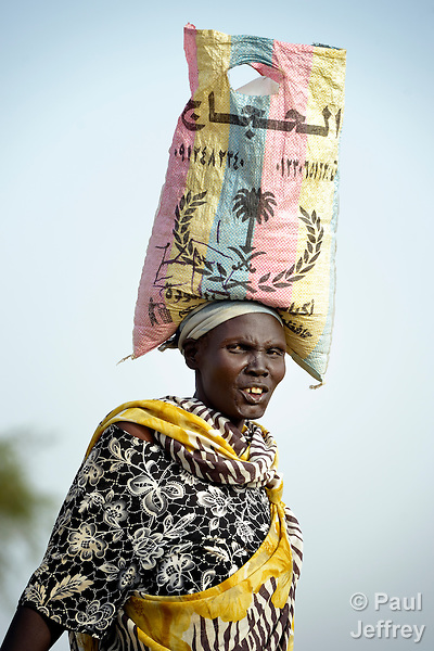 A displaced woman carries supplies in a bag on her head in Agok, a town in the contested Abyei region where tens of thousands of people fled in 2011 after an attack by soldiers and militias from the northern Republic of Sudan on most parts of Abyei. Although the 2005 Comprehensive Peace Agreement called for residents of Abyei--which sits on the border between Sudan and South Sudan--to hold a referendum on whether they wanted to align with the north or the newly independent South Sudan, the government in Khartoum and northern-backed Misseriya nomads, excluded from voting as they only live part of the year in Abyei, blocked the vote and attacked the majority Dinka Ngok population. The African Union has proposed a new peace plan, including a referendum to be held in October 2013, but it has been rejected by the Misseriya and Khartoum.