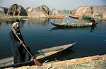 Marsh Arabs. Southern Iraq. Circa 1985. Marsh Arab man and woman in boats. Transport between islands known as dibin. Reed island houses.