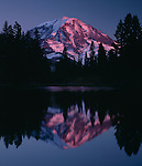 A glowing Mt. Rainier is reflected in the waters of Eunice Lake, Washington.