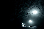 Black and white image of a person running from something on a foggy night. Shot in Prospect Park, Park Slope, Brooklyn, New York City.