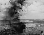 As advancing Marines limited the areas left to the Japanese on Guam, they still managed to form small kernels of resistance in caves and dugouts that ran for nearly a half a mile. Marine engineers used high explosives to blow up the cover but the Japanese immediately opened fire following this photograph. The engineers placed more TNT to silence the fire.