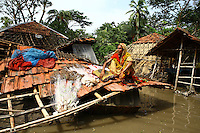 A woman sits on the roof of her destroyed home. Thousands of people were displaced in Shyamnagar Upazila, Satkhira district after Cyclone Aila struck Bangladesh on 25/05/2009, triggering tidal surges and floods..