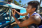 Jimmy Cabrillos disassembles his fishing boat in order to properly rebuild it. The boat was damaged during Typhoon Haiyan, which ravaged a wide swath of the Philippines in November 2013. Cabrillos lives on Manipulon, a small island off the coast from the town of Estancia. The storm was known locally as Yolanda. Residents of this island have received assistance from the ACT Alliance.