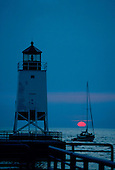 Charlevoix Lighthouse, Charlevoix, Michigan, Lake Michigan with sailboat at sunset.