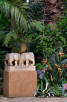 A plinth featuring carved stone elephants occupies a spot in the garden