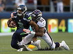 Seattle Seahawks quarterback Russell Wilson is hauled down by Denver Broncos Wesley Woodyard at CenturyLink Field in Seattle, Washington on  August 17, 2013. The Seattle Seahawks beat the Broncos 40-10.     ©2013. Jim Bryant Photo. All Rights Reserved.