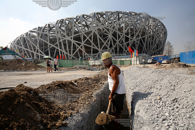 """A construction worker digs a ditch in front of the Beijing Olympic Games' National Stadium, """"The Bird's Nest""""."""