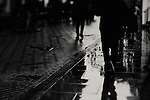 peoples legs walking down a street, blurred as they walk fast in the rain, reflections seen in the puddles & shadows all around