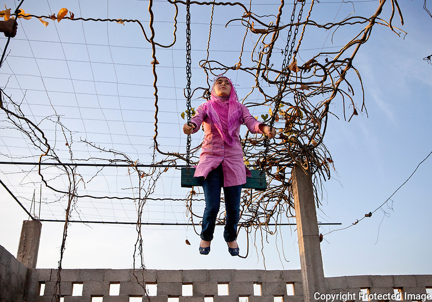 """Young girl relaxes at her family farm """"vacation"""" spot on the outskirts of Gaza city. Travel is next to impossible for the majority of Gazans due to the siege, but the Palestinians remain creative and hopeful. BBQs with the family remains a top day off from school for these young girls."""