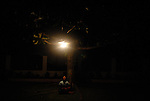 A Filipino girl watches bugs swarm around an outdoor light in Ilocos Norte, Philippines..**For more information contact Kevin German at kevin@kevingerman.com
