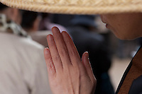 A Female monk or nun in a traditional hat blesses people at the entrance to Togan-jio temple in Sugamo, an area of Tokyo popular with older people. Japan Tuesday, November 24th 2009