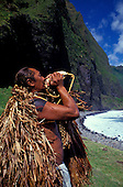 "EDITORIAL ONLY. Man in traditional """"rain cape"""" blowing conch shell. Waikolu Valley, Molokai"