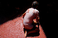 A girl kneels in tomato pulp during La Tomatina festival in Bunol, Spain, 31 August 2006. La Tomatina is a tomato fight held annually in the town of Bunol, close to Valencia. Approximately 40,000 people from all over the world arrive to fight in the battle in which about 50 tons of over-ripe tomatoes are thrown in the street. During the one hour battle everybody fights everybody by throwing squashed tomatoes. The origin of this event is unknown but the Tomatina fights have been recorded since 1945.