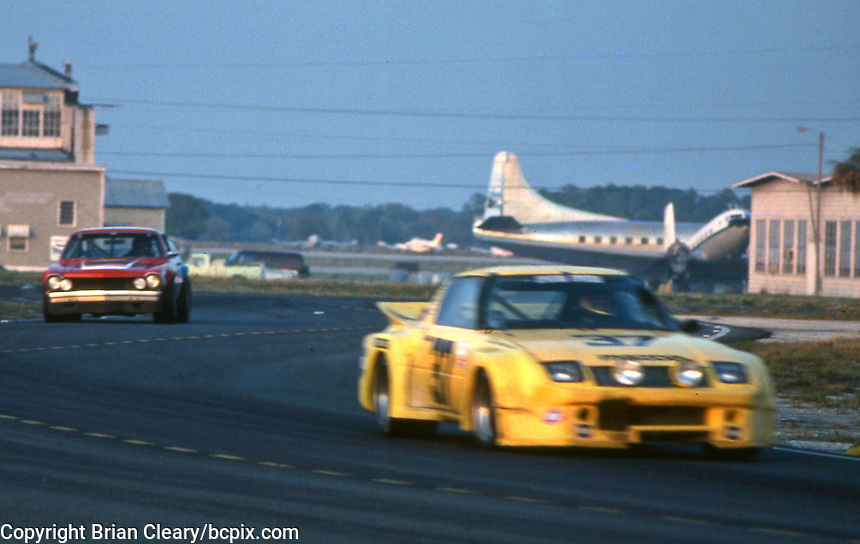 A pair of cars race past airplanes at the 12 Hours of Sebring endurance sports car race, March 19, 1983. (Photo by Brian Cleary/www.bcpix.com)