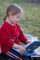 Kid Girl Playing Laptop Computer in Yard
