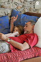Father reading book with daughter lying on sofa (Licence this image exclusively with Getty: http://www.gettyimages.com/detail/81867358 )