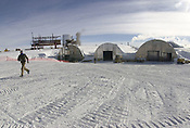 A worker in the garage area of Amundsen Scott South Pole station in 2001. The new station structure rises in the background