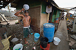 A man bathes in the morning outside his temporary shelter in Tacloban, a city in the Philippines province of Leyte that was hit hard by Typhoon Haiyan in November 2013. The storm was known locally as Yolanda. The ACT Alliance has been active here and in affected communities throughout the region helping survivors to rebuild their homes and recover their livelihoods.