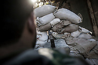 An FSA rebel fighter stands guard behind a barricade at the front line in Bab Al-Nasr, a neighborhood in the Old town of Aleppo City.
