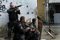 Policemen take position during operation at Vila Cruzeiro slum, Rio de Janeiro, Brazil, November 25, 2010. Authorities in Rio de Janeiro try to control a fourth day of violence apparently orchestrated by drug gang members who have attacked police stations and burned cars in Rio de Janeiro city as protest by traffickers after being forced from their turf by police occupations of more than a dozen slums in the past two years..(Austral Foto/Renzo Gostoli)