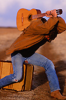 man sitting on a suitcase and smashing a guitar while on a dirt road