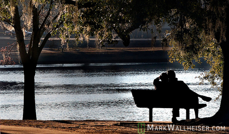 A young couple sit along the east side of Lake Ella on a recent afternoon as the sun retires and the winter cold comes alive in Tallahassee, Florida.   (Mark Wallheiser/TallahasseeStock.com)