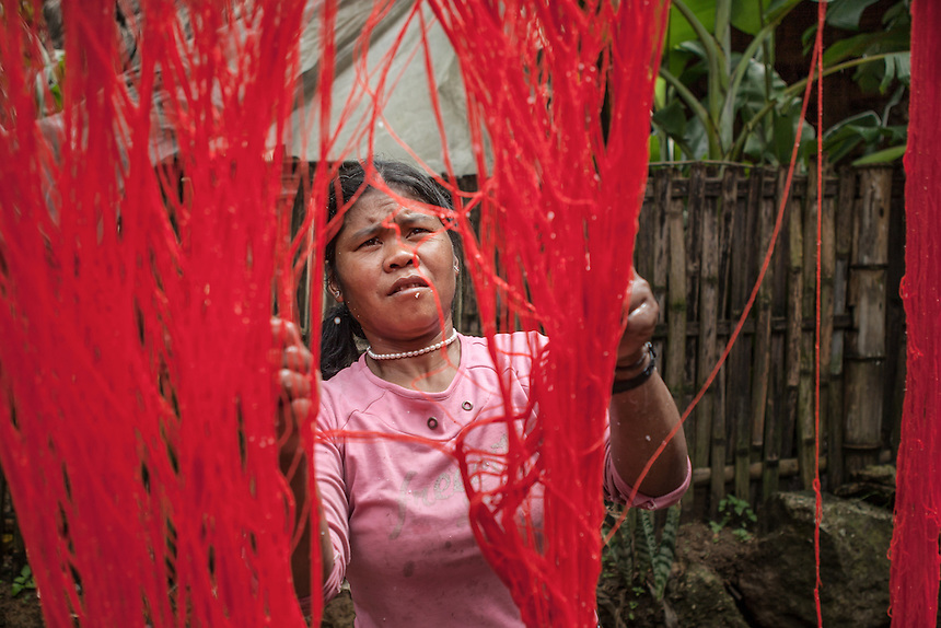"""A Wa woman drying her weaving material in the village of Wengding. Wa people produce their own clothes and wear it with dignity. The Wa, which literally means """"mountain dwellers"""", is the hilltribe that inhabit the Sino-Burmese. Known as one of the last headhunting tribe until mid-twentieth century, their population in both countries now approximately no more than one million. In the homogenous society of modern China, Wa is one of more than 50 officially state-recognized ethnic minorities. They can be found around the southwestern corners of Yunnan province."""