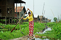 A girl rows her canoe on a canal. Canals substitute streets and canoes are the only means of transport in villages built on water.