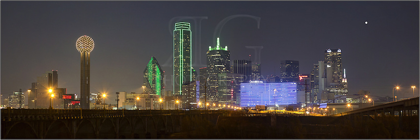 Reunion Tower is a Dallas icon. In this Dallas skyline panorama, the golden tower, along with other prominent high rises, light up the downtown area from the banks of the Trinity River.