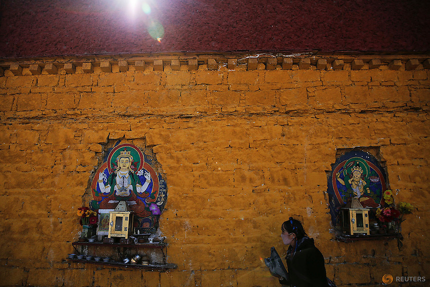 A Tibetan woman prays along walls of the Potala Palace in Lhasa, Tibet Autonomous Region, China November 17, 2015. The Potala Palace, once the seat of Tibetan government and traditional residence of Dalai Lama, is a 13-storey, 1000-room palace that is more than 1,300 years old and is more than 3,700 meters above sea level. It is a UNESCO World Heritage site. REUTERS/Damir Sagolj