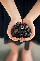 Woman with a handful freshly picked blackberries