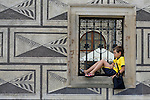 A boy rests in the window of the Schwarzenberský Palác on the Hrad?anské Nam in Prague.