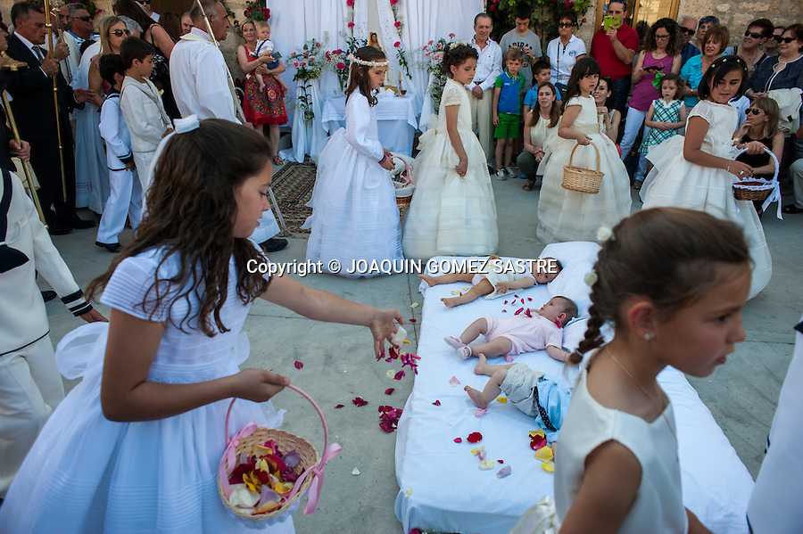 Children who miss the first communion throw flower petals to babies after they jump to bless them